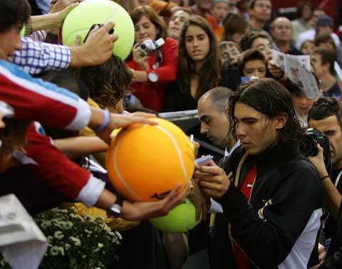 Rafa Nadal firmando autógrafos en pelotas