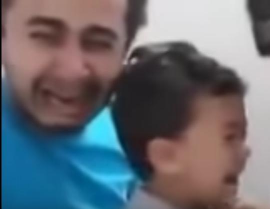 Un padre que llora desconsolado al vacunar a su hijo